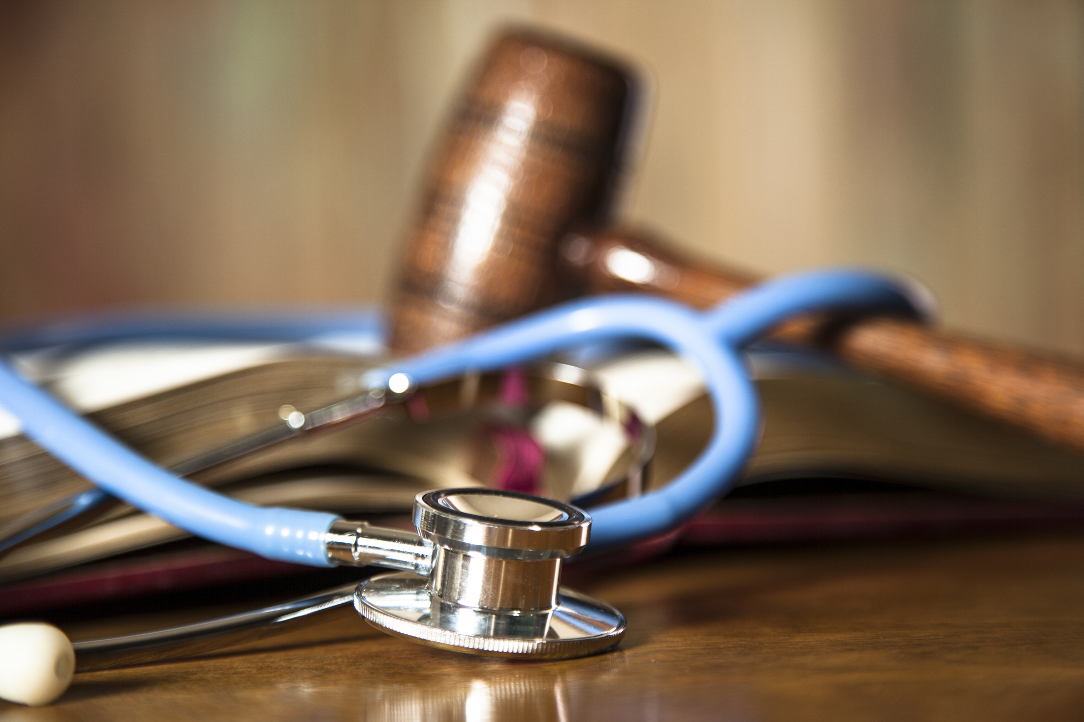 Judge's gravel and blue stethoscope on court room table