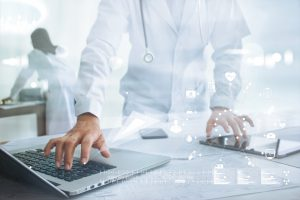 Doctor on tablet and laptop with medical icons