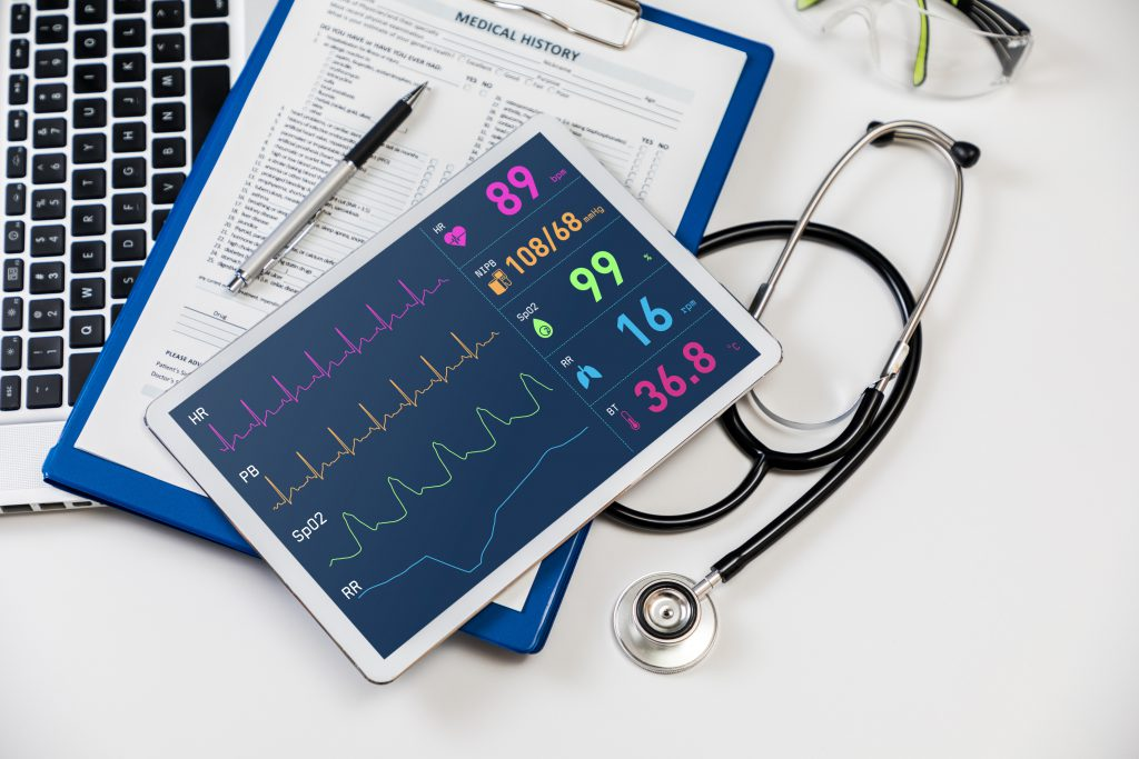 Tablet with vital signs, clipboard with medical history and stethoscope lying on laptop keyboard