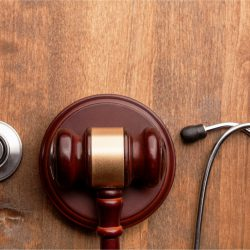 Gavel with stethoscope on wooden surface