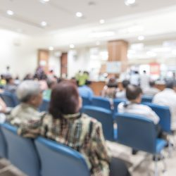 Blurred hospital waiting room full of people in blue chairs