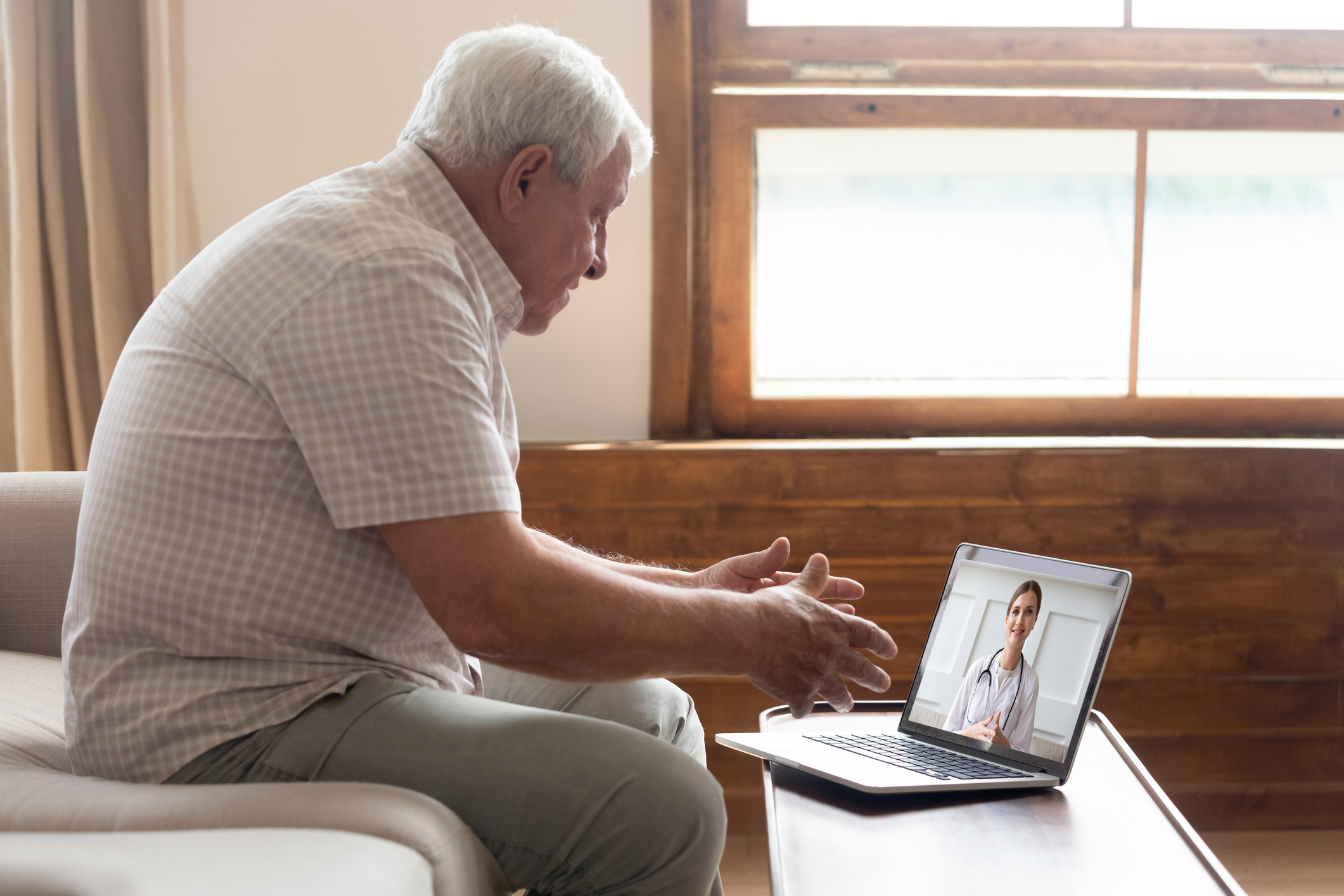 Telehealth conference between an elderly man and his doctor