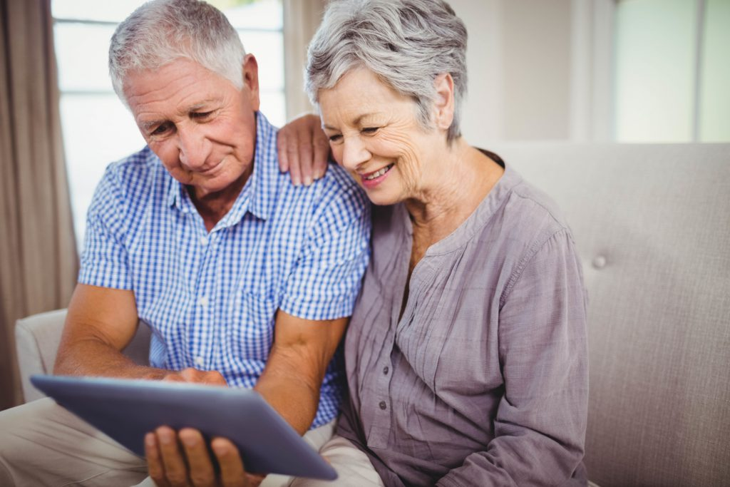 Elderly male and female on couch with tablet in hand