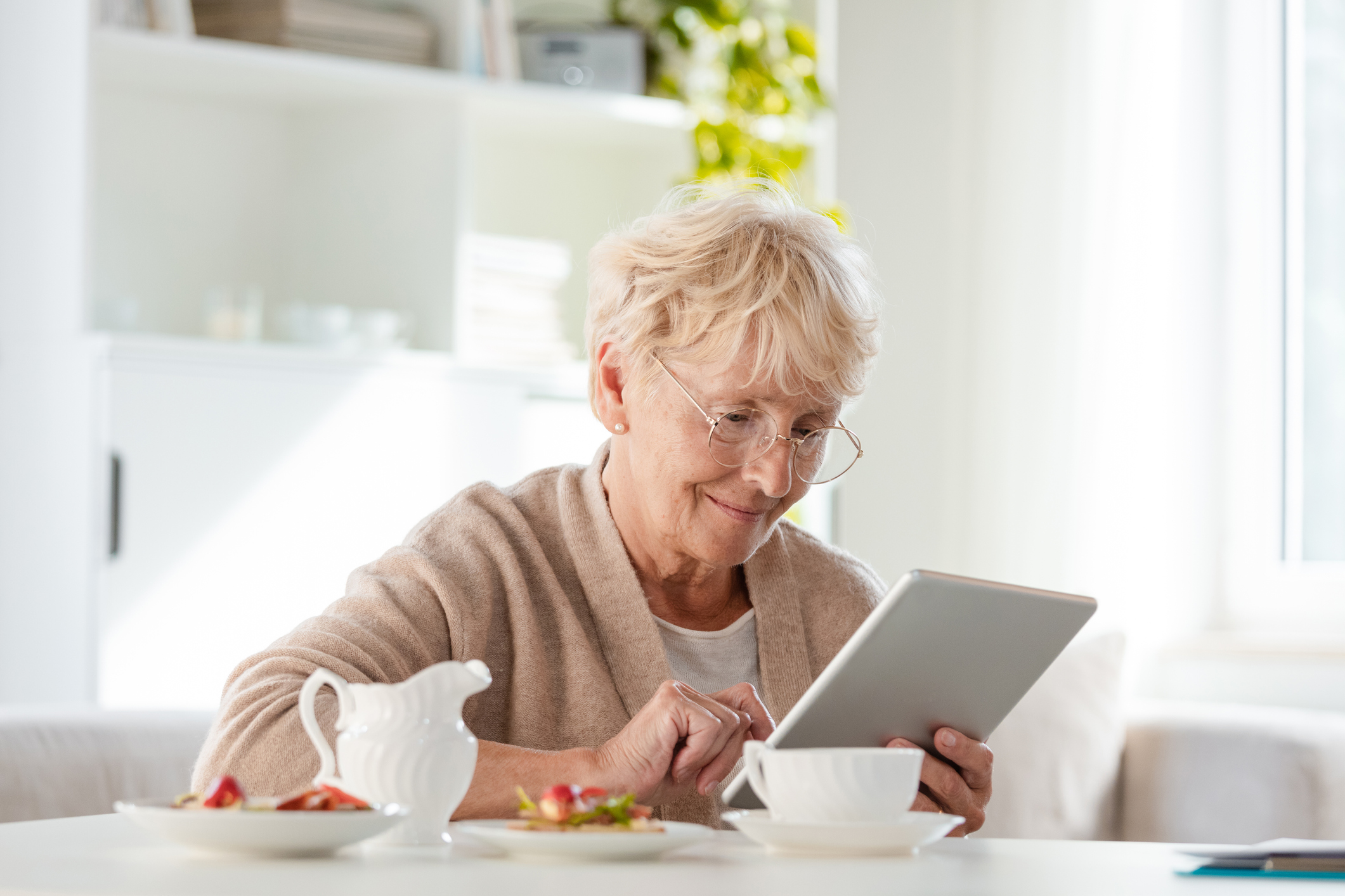 elderly woman siting at kitchen counter on tablet