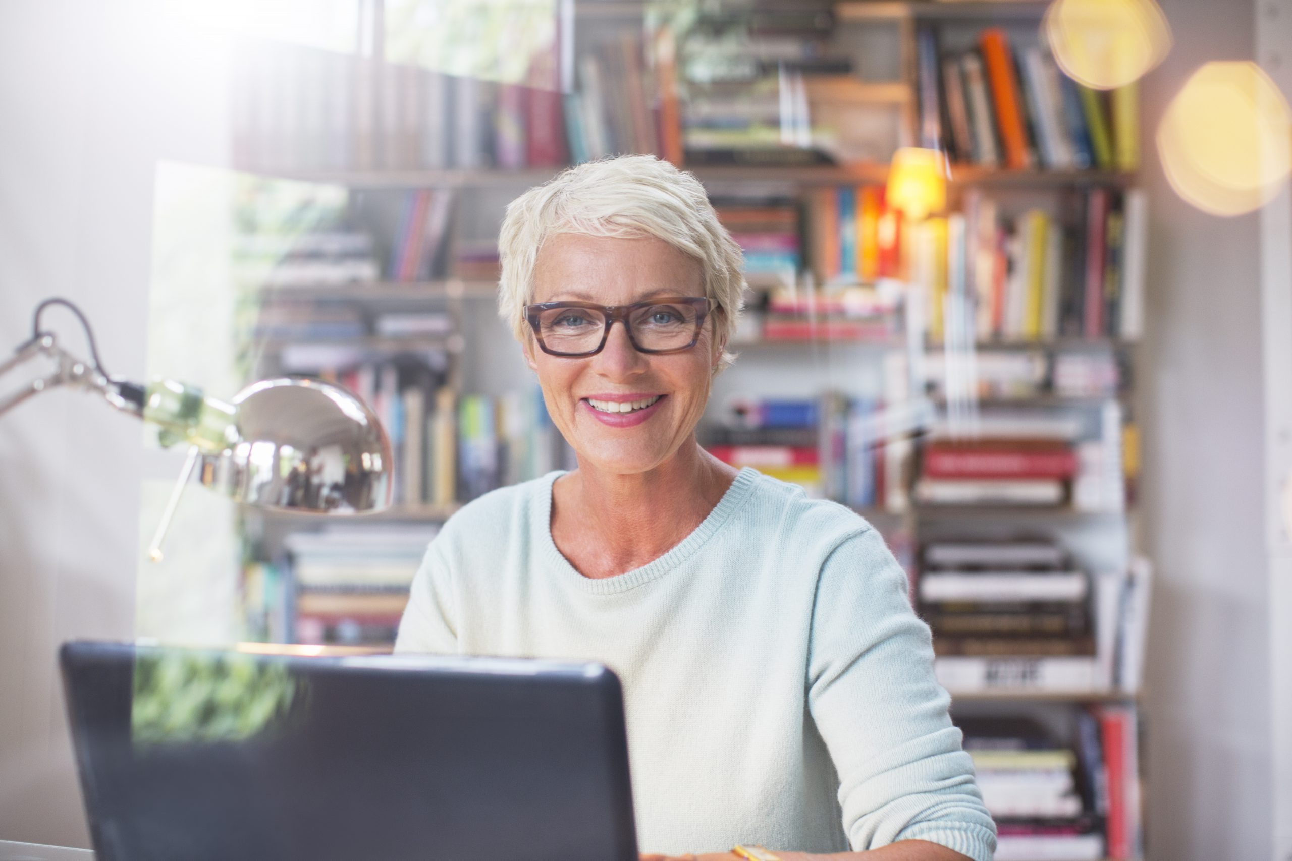 Elderly female with glasses sitting in front of laptop with books in the background