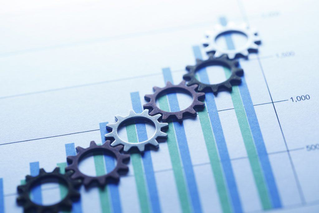 blue gears sitting on a bar chart with blue and green increase bars