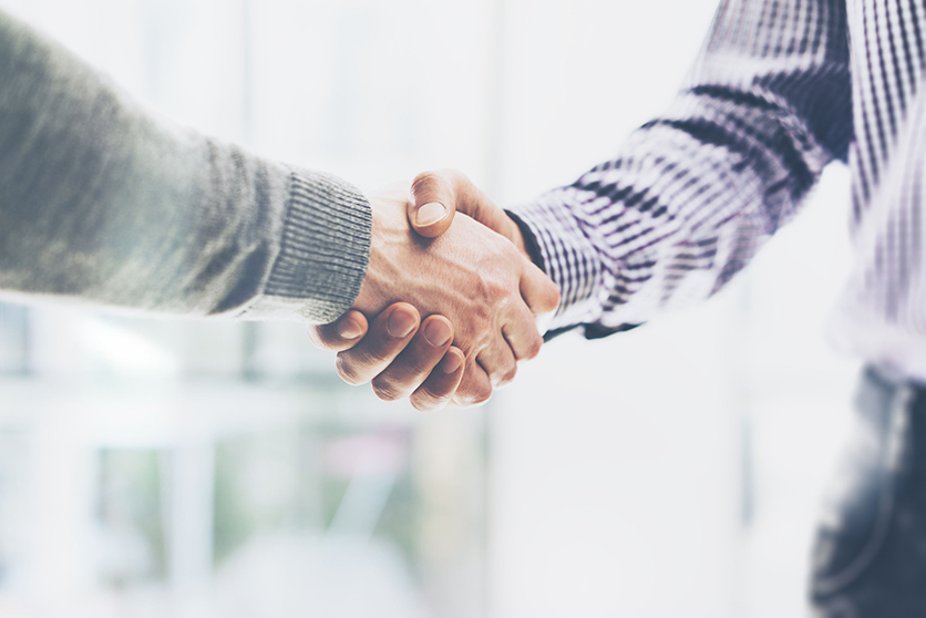 two male shaking hands over blurred background