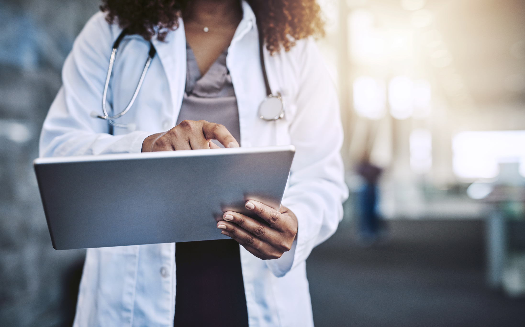 African American female doctor in white coat on a tablet