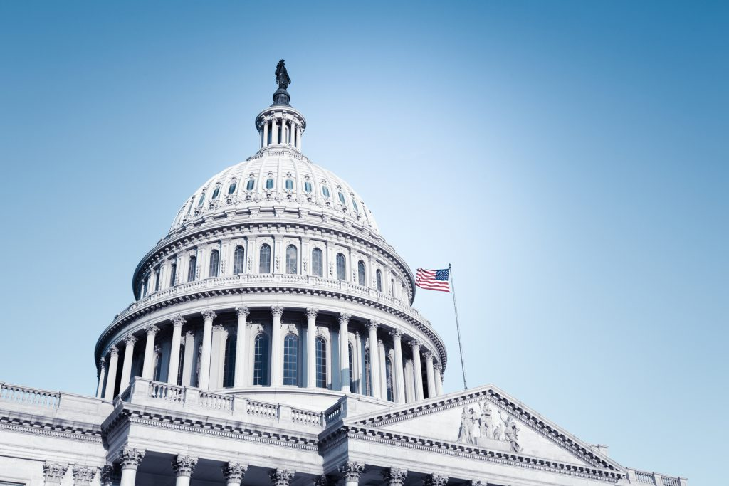 Cropped United States Capitol building with flying American Flag