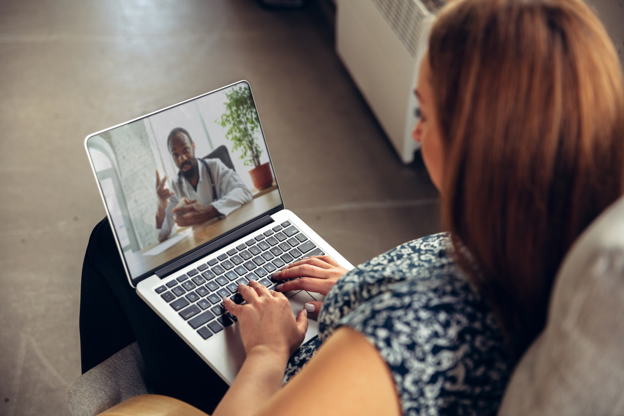 Woman on telehealth call on laptop with male doctor
