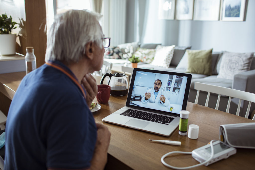 Elderly man on telehealth call with male doctor