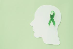 Green mental health awareness ribbon on white head cut out